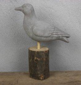 Cementen vogel op houtblok