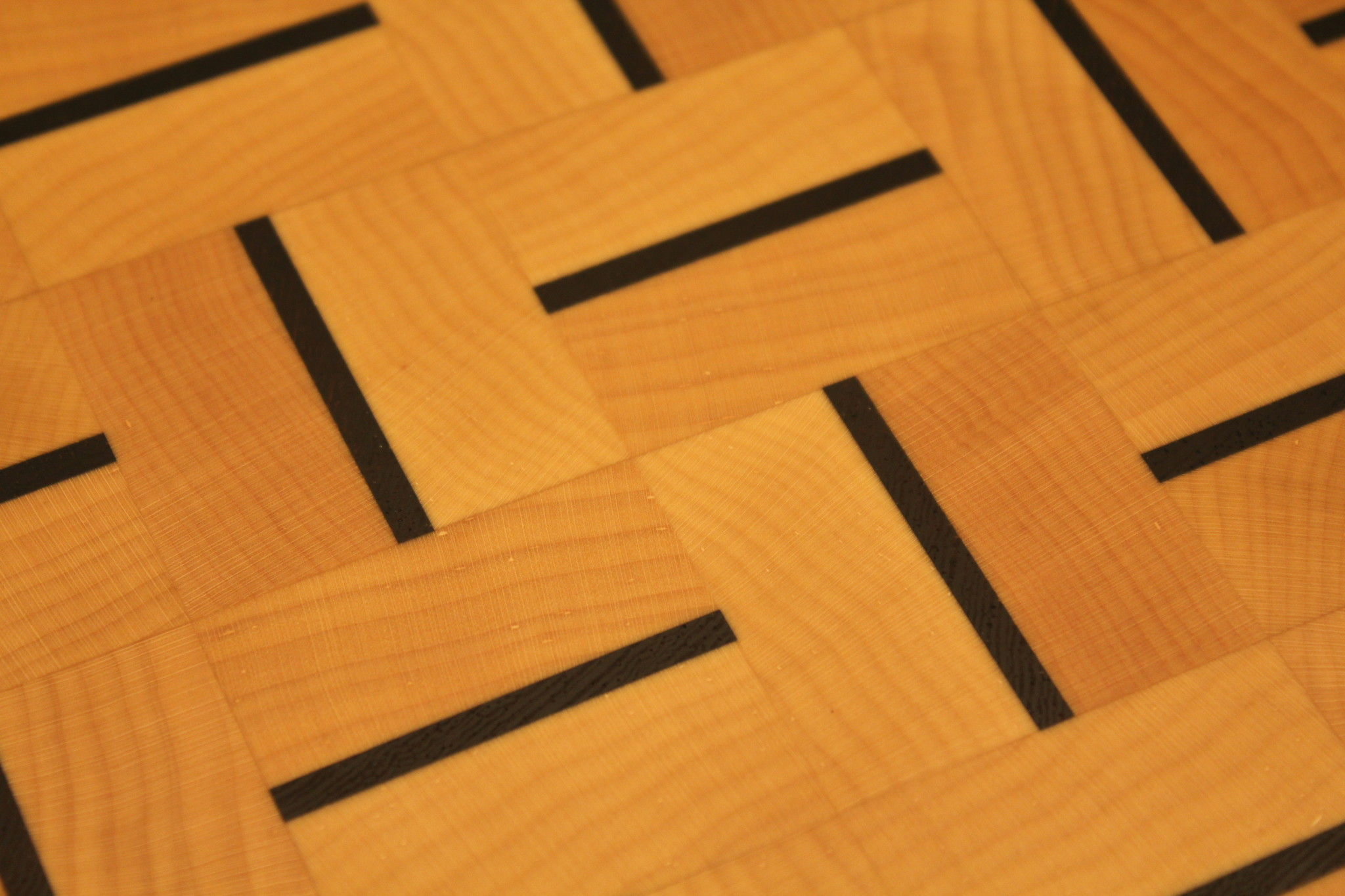 End grain cutting board of hard maple alternating stripes of dark African wenge