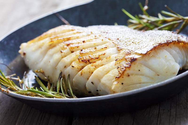 Kabeljauwfilet in botersaus, gekookte aardappelen en bospeen