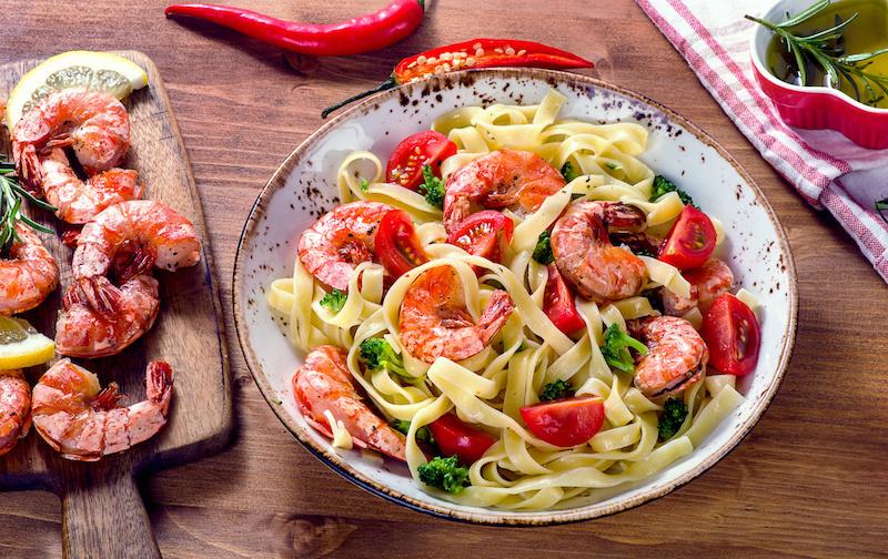Pasta van tagliatelle in tomatenroom met groenten en gamba's