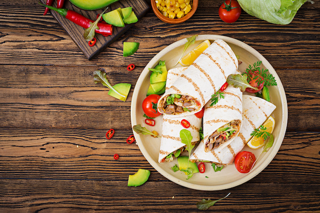 Mexicaanse burrito gevuld met gehakt, groenten, kaas & komkommersalade