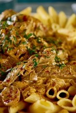 Pasta van penne met kipdij en groenten in stroganoff saus