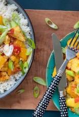 Rijstschotel rijk gevuld met groenten, kipkluifjes en gebakken mango