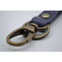 Sleutelhanger met naam gemaakt van nikkelvrije bronzen delen met blauw Italiaans volnerf leer