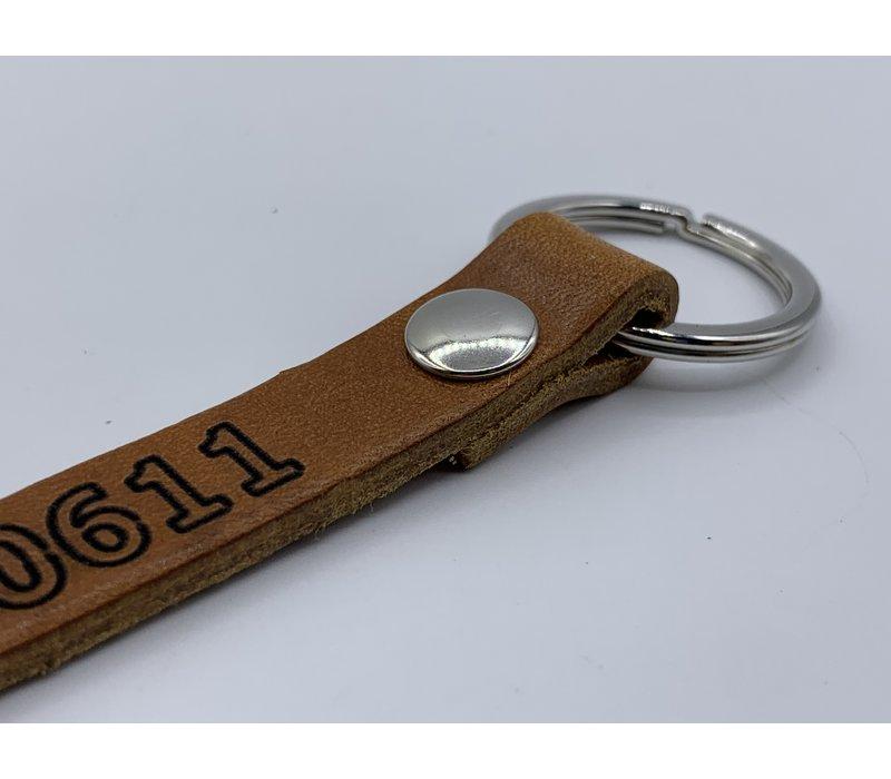 Cognac sleutelhanger met zilver kleurige ring en eigen telefoonnummer of korte tekst.