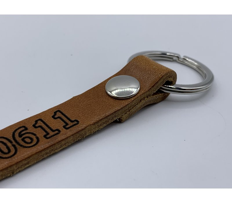 Cognac sleutelhanger met zwart kleurige ring en eigen telefoonnummer of korte tekst.