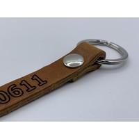 Sleutelhanger met bronzen ring en eigen telefoonnummer of korte tekst.