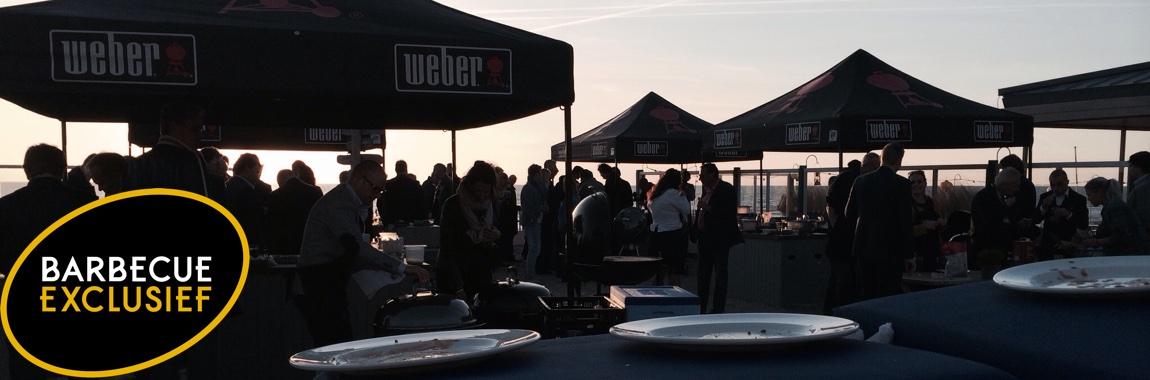 Een bedrijfsbarbecue in volle gang met de ondergaande zon.