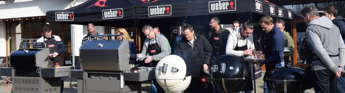Een barbecue workshop met verschillende bbq's waar mensen culinair leren buiten koken.