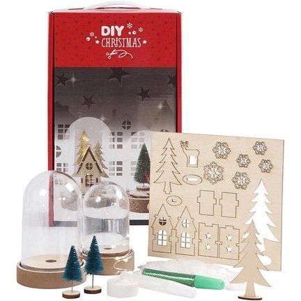 Kit med 2 klokker af plastikglas på løs jord og forskellige materialer til en lille julescene under hver klokke.