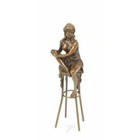 Een bronzen sculptuur van een vrouw op barkruk