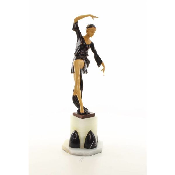 A large bronze sculpture of a graceful dancer with wooden inlay