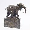 Een bronzen sculptuur van een lopende olifant