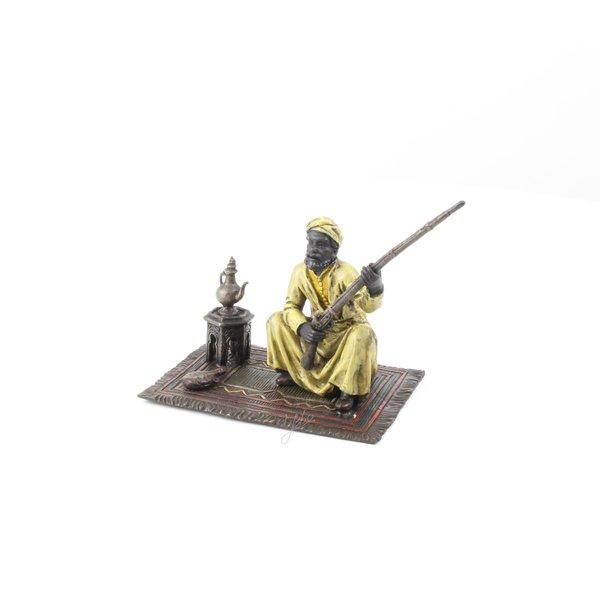 Een bronzen sculptuur van een Arabische stamlid op een tapijt