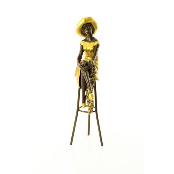 Bronze sculpture of a female on a bar stool