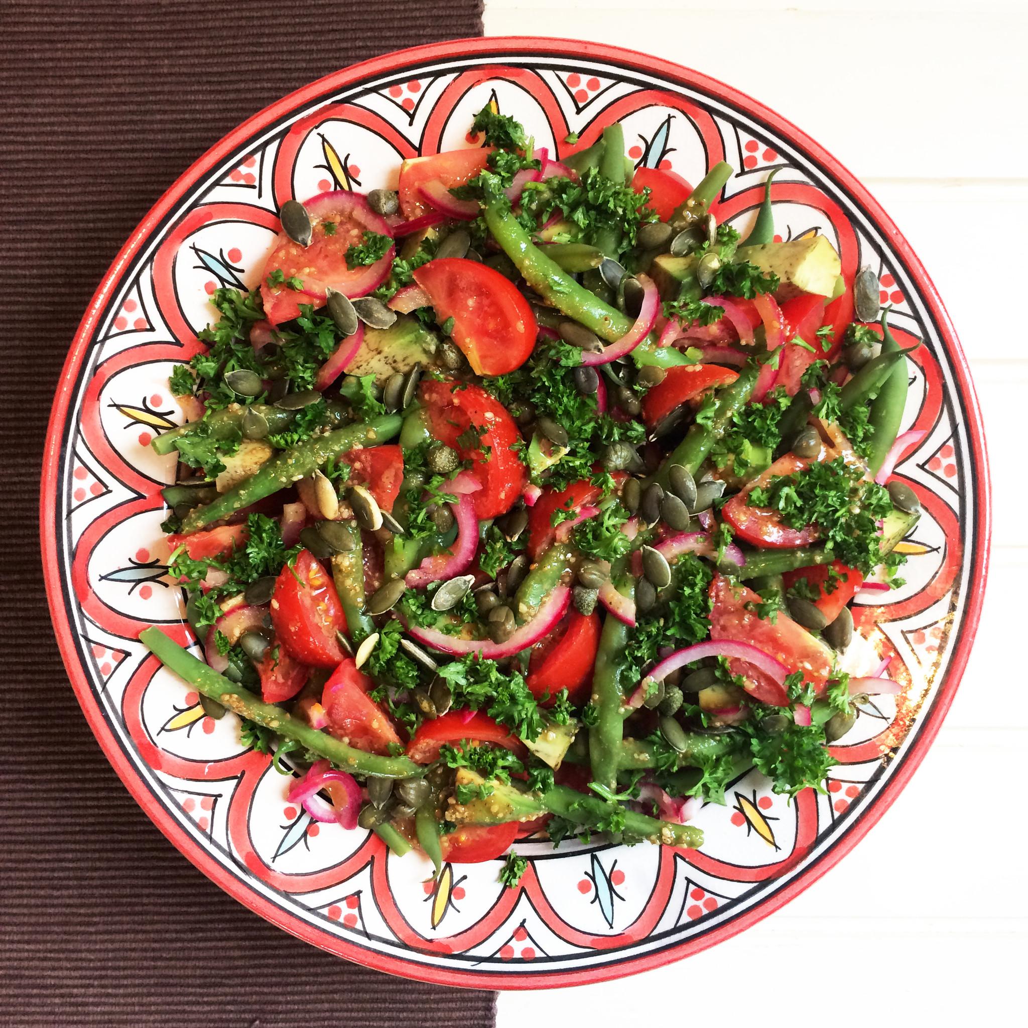 Sperziebonen-tomatensalade met avocado en tahindressing op bord