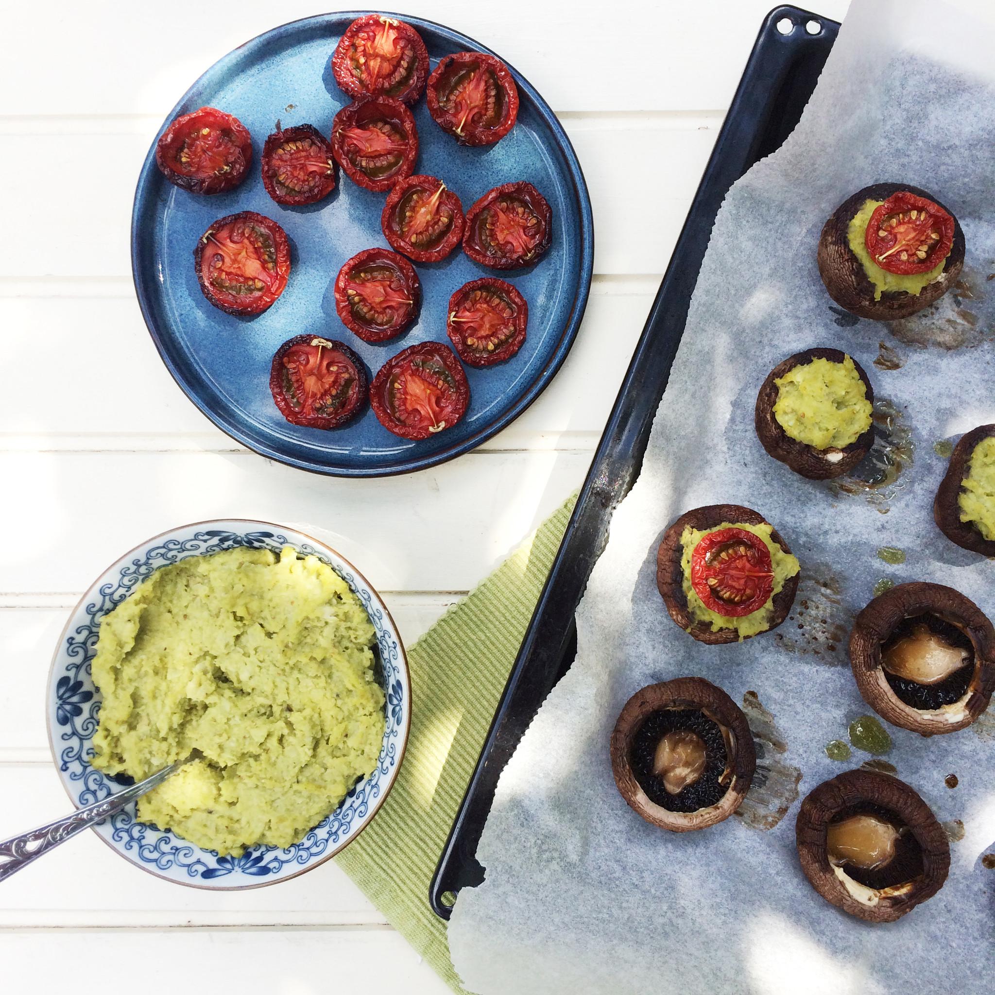 Gevulde kastanjechampignons met tuinbonen en tomaat op bord en bakplaat