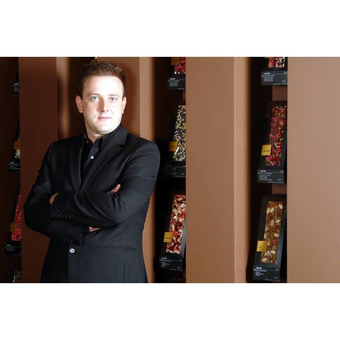 - ENTRÉE | SYRAH II | Valrhona dunkle Schokolade 66% mit Pistazien aus Bronte, kandierte Veilchen und gefriergetrocknete Schwarze Johannisbeere, 100g
