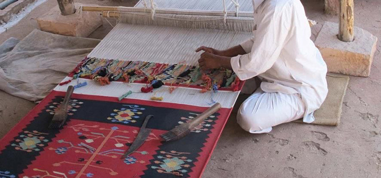 father weaving rug india