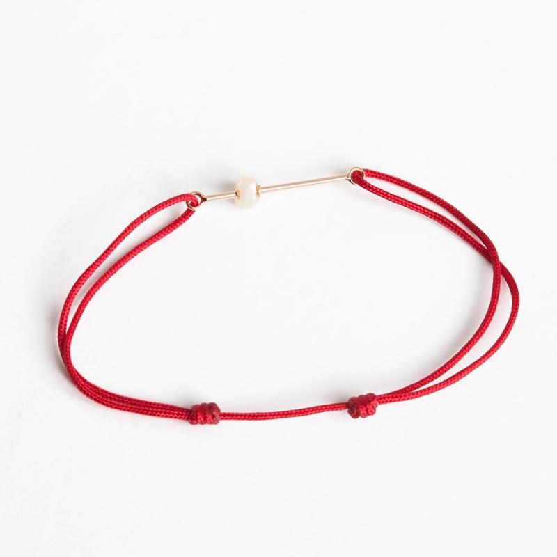 Tiny Om Pearl bracelet on thread