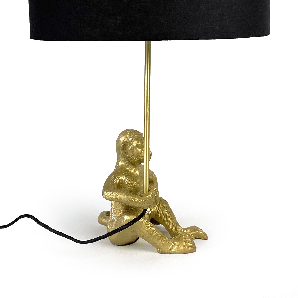 Gold monkey table light with black lamp shade