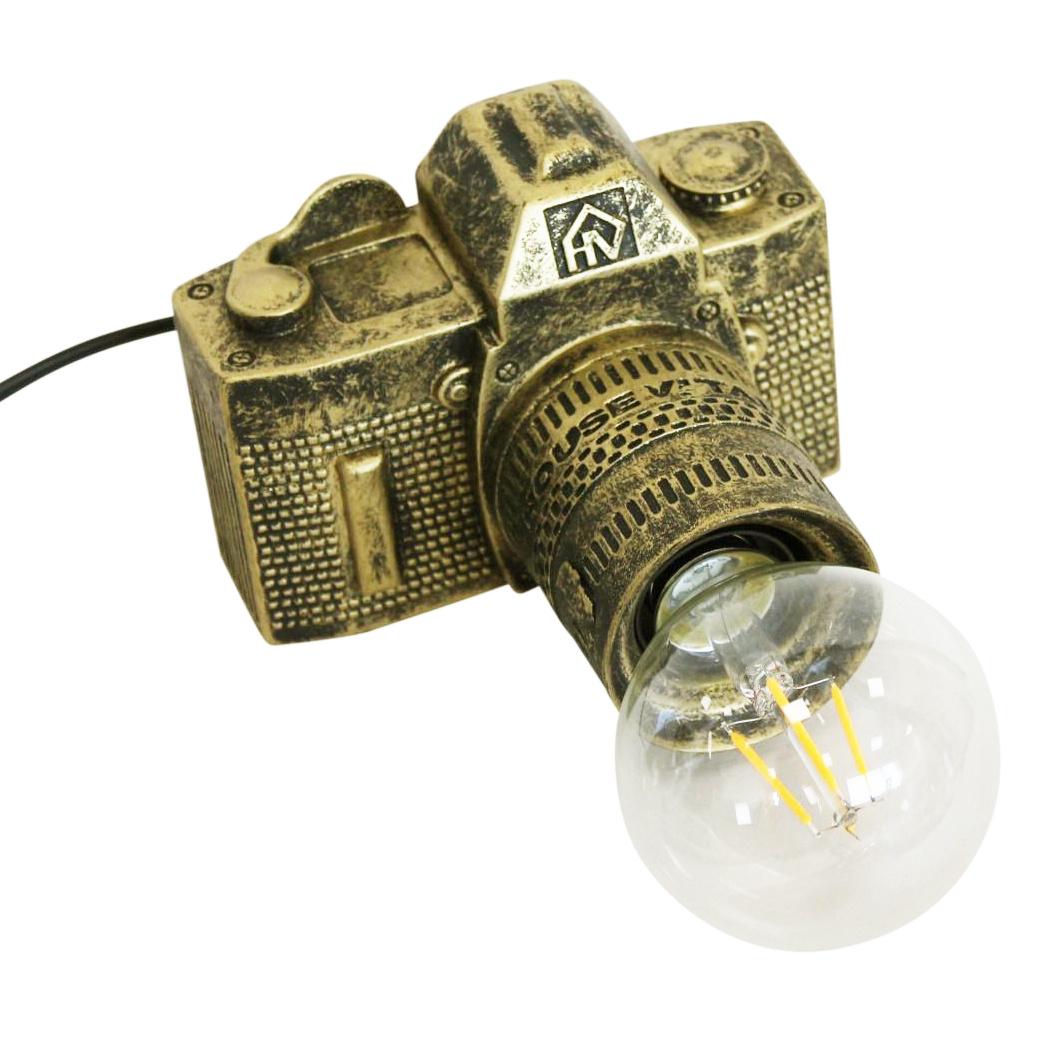 Gouden lamp in de vorm van een fotocamera