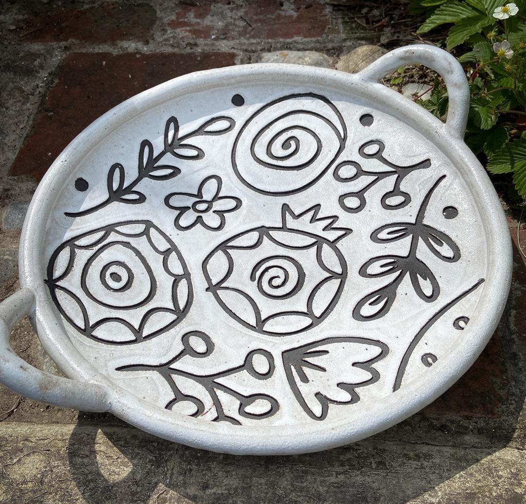 Handbuilt round stoneware platter in black clay with white stone glaze. Floral pattern, round with handles. dia: 400mm