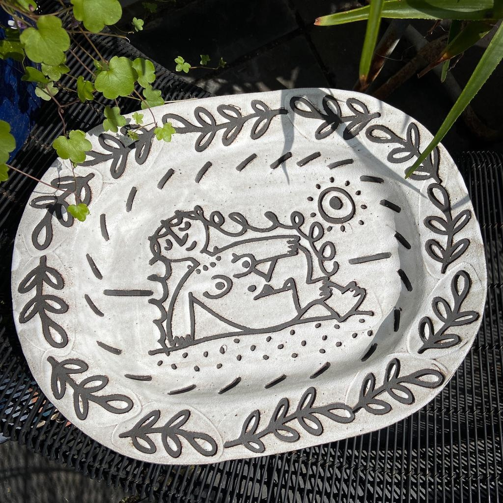 Handbuilt embossed stoneware platter in black clay with white stone glaze. Nude woman with leaves border. 420mm x 330mm