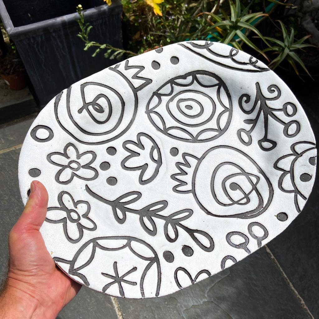 Handbuilt embossed stoneware platter in black clay with white stone glaze. Floral pattern. 420mm x 330mm
