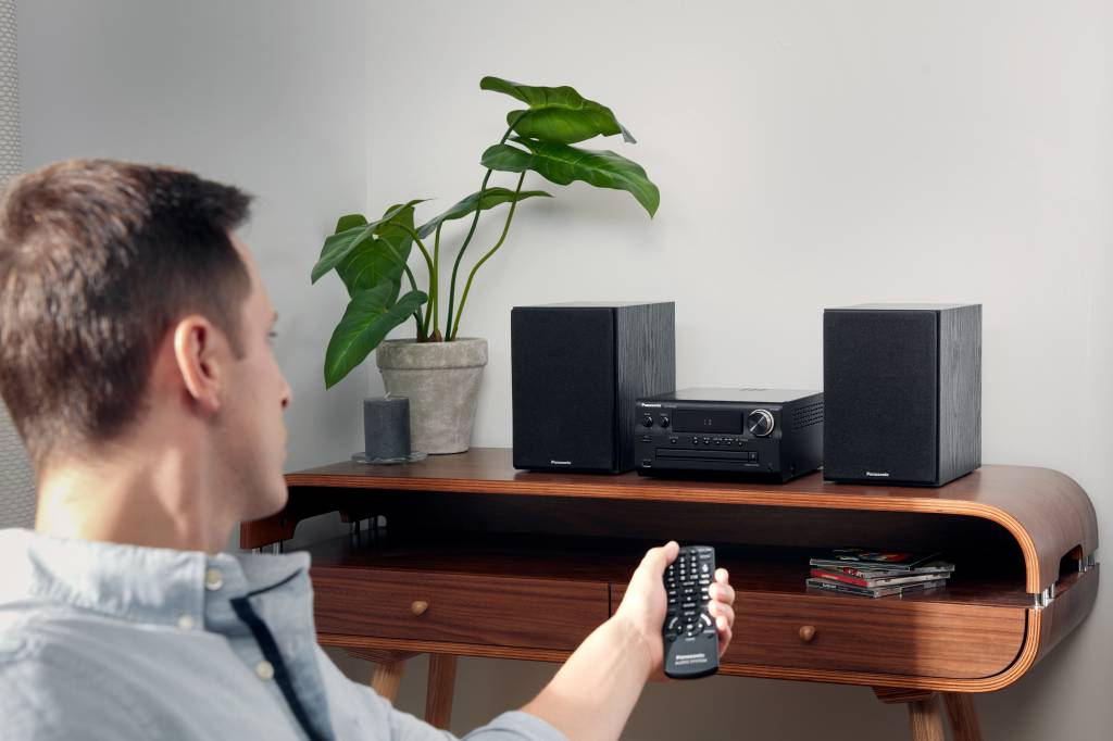 man turning up a stereo during a party