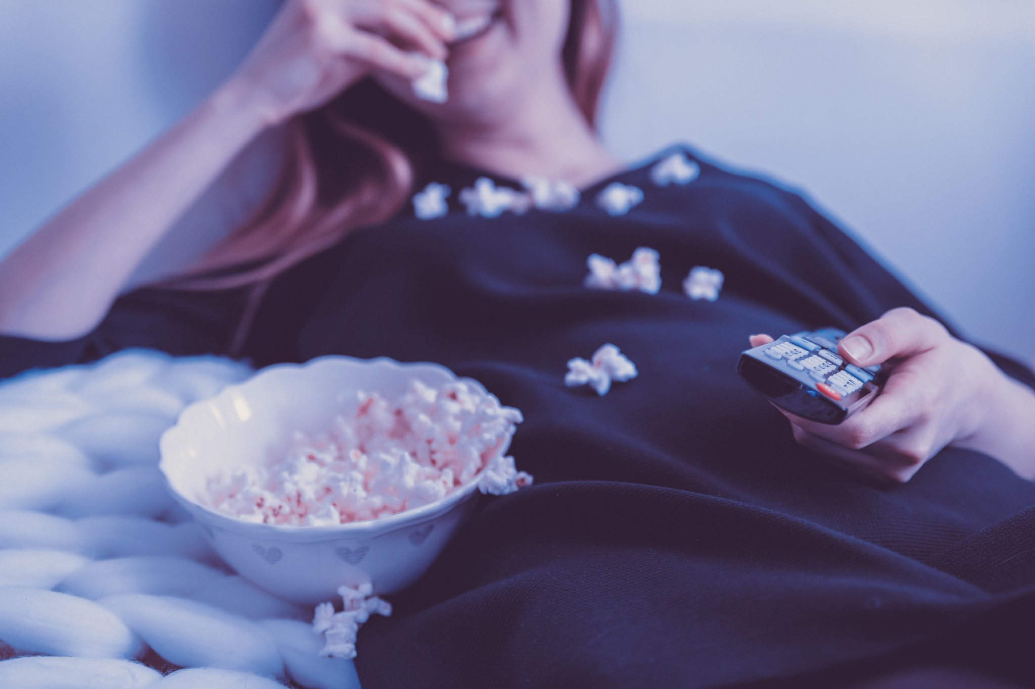 a person watching tv with popcorn