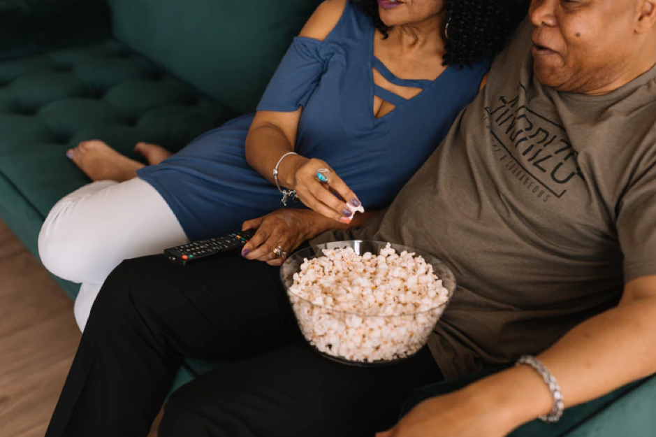 Couple sitting on the sofa relaxing watching a film with a bowl of popcorn