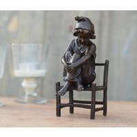 Beeld brons meisje zittend op een stoel
