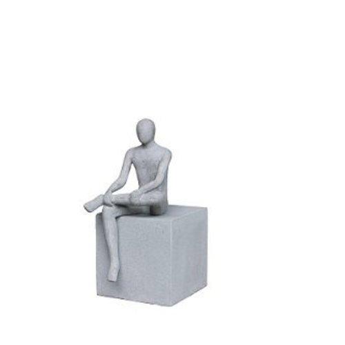 Beeld zittende man op kubus