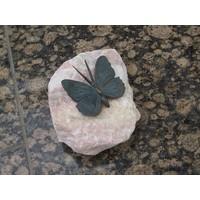 Bronzen vlinder op roze steen