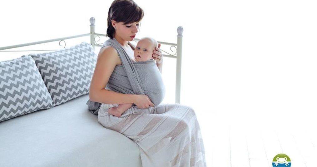 Het dragen van een pasgeboren baby in een draagdoek of draagzak.