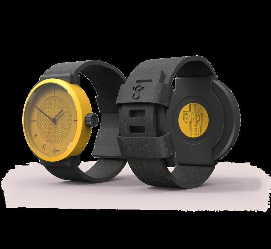 Een circulair dameshorloge met geel/zwarte kast en een zwarte band van Circular Clockworks