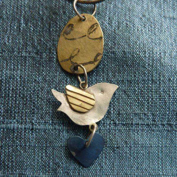 Pájaro de plata y latón con disco y collar de corazón titaniam