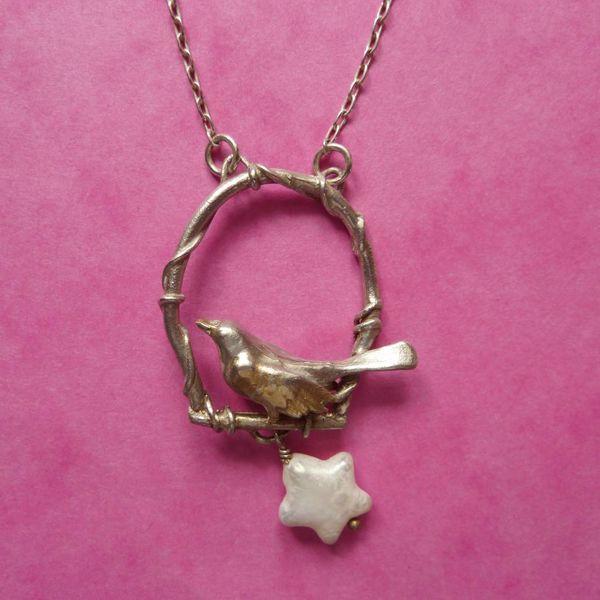 Bronce pájaro en columpio de plata con collar de estrellas de oro y perlas