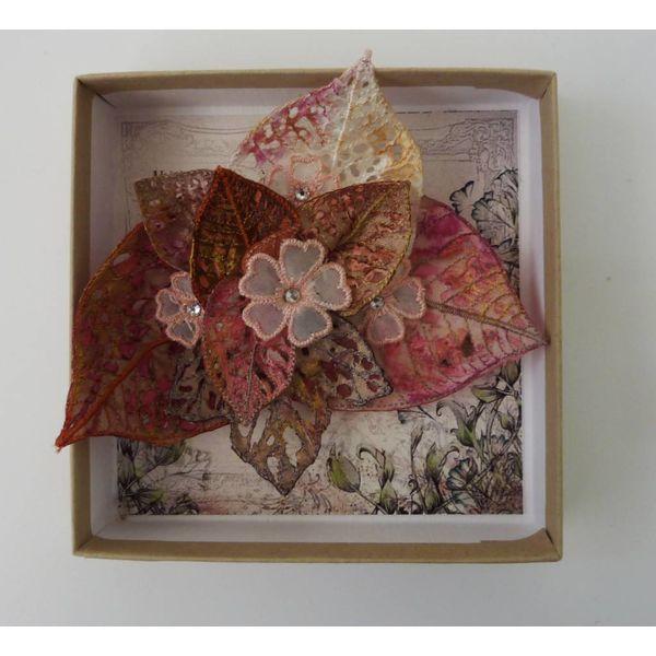 Broche bordado con racimos de hojas y flores