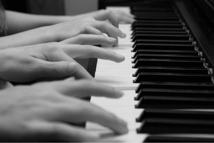 Twee personen spelen samen piano