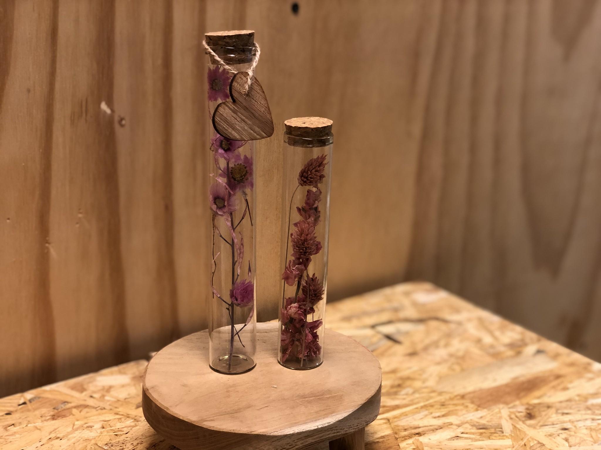 Glazen buizen met roze droogbloemen