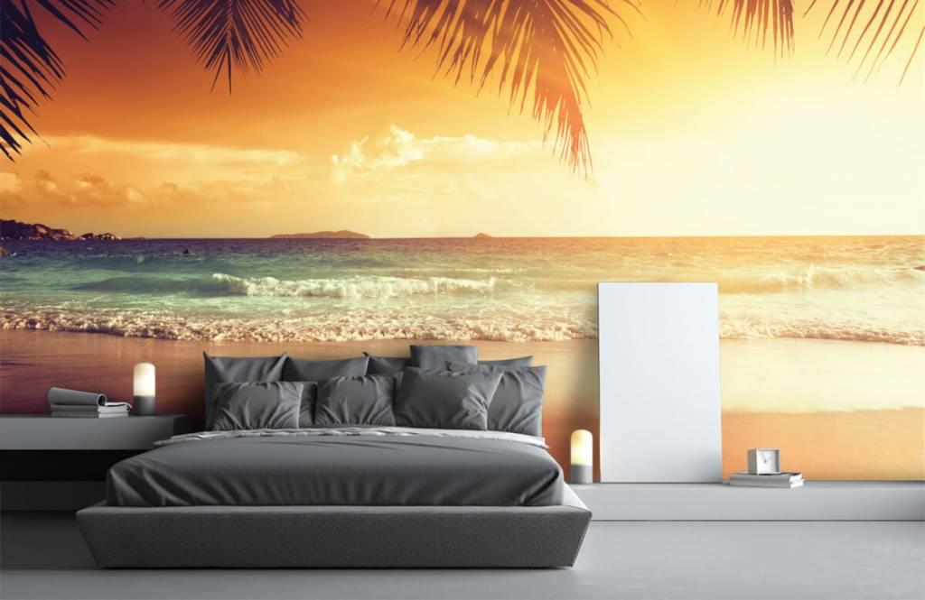 Behang met een oranje zonsondergang fotobehang