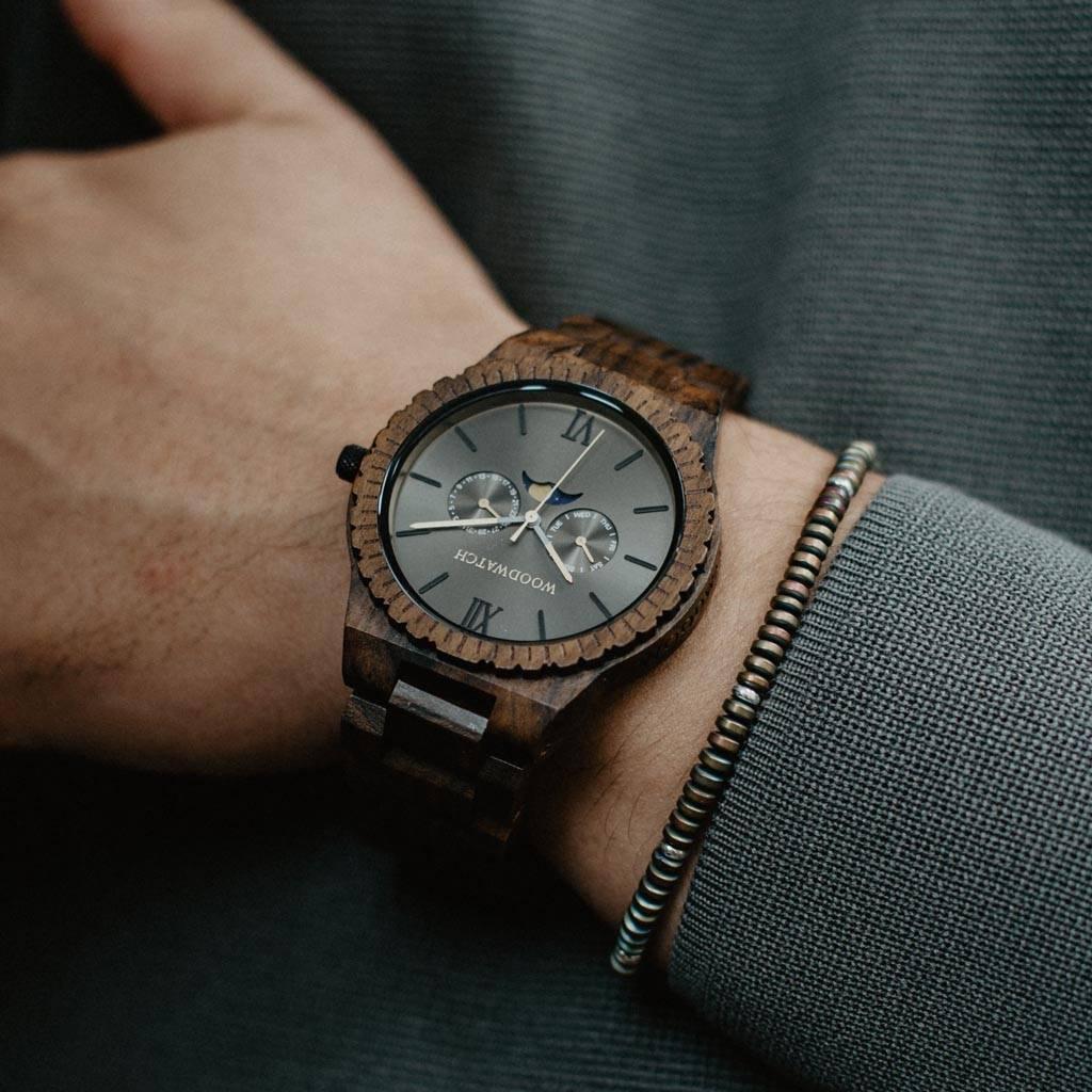 Diese Premium-Uhr mit Mondphasenanzeige kombiniert einzigartige neue handgefertigte Holzarten mit luxuriösen Edelstahl-Zifferblatt und -Gehäuseboden. Im Mittelpunkt der Uhren steht ein komplett neues Multifunktionswerk mit zwei zusätzlichen Hilfsziffern m