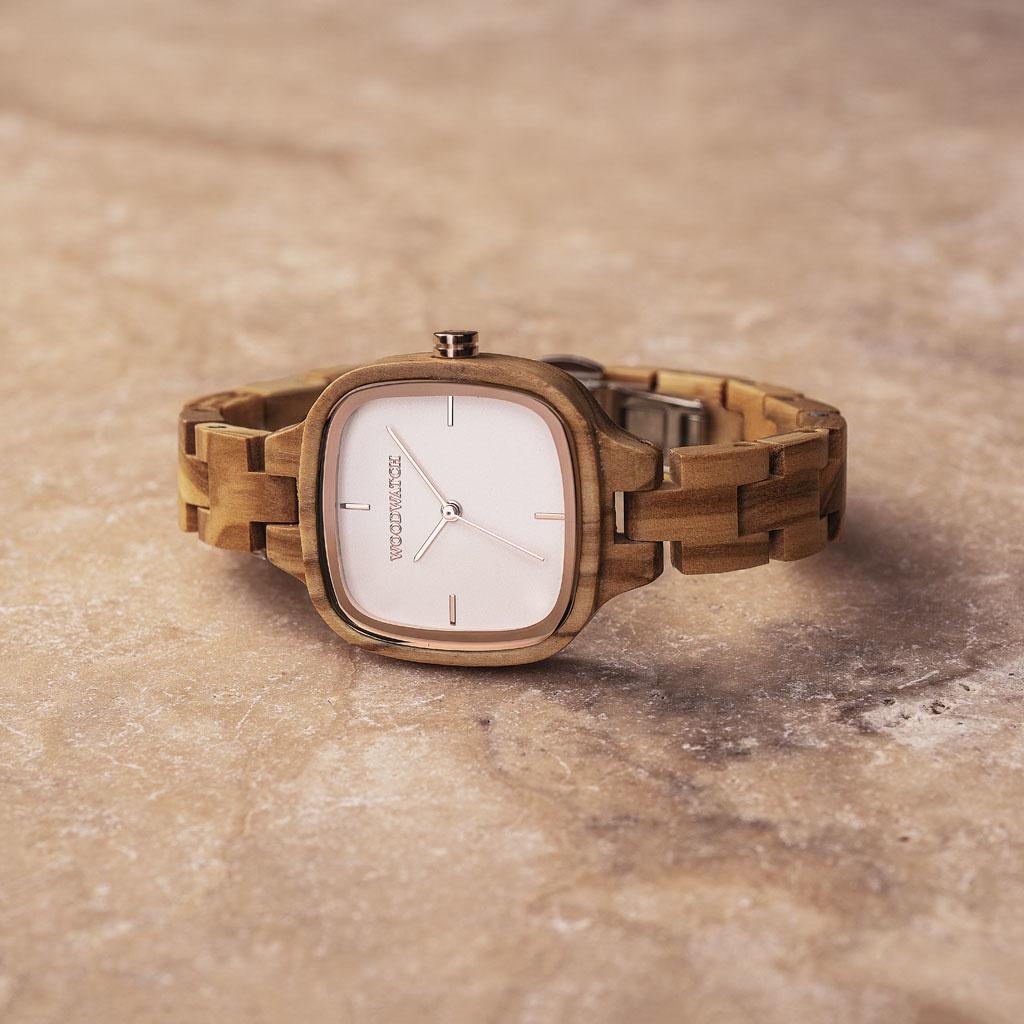 Questo orologio ha una cassa quadrata con un bianca quadrante e dettagli color argento brillante. Il cinturino è realizzato in legno d'ulivo naturale fatto a mano e rifinito alla perfezione per creare i nostri più recenti motivi per cinturini sottili.