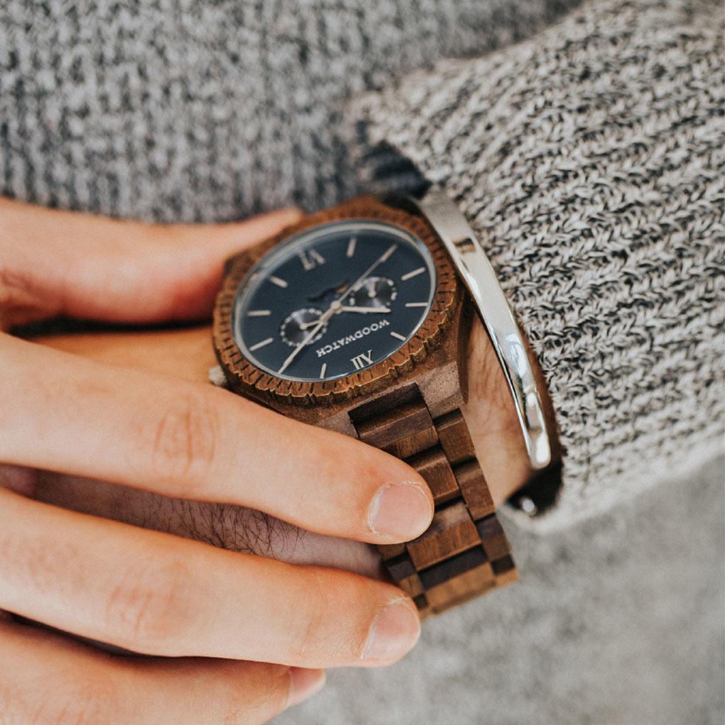 Diese Premium-Uhr kombiniert natürliches Holz mit einem luxuriösen Edelstahl-Zifferblatt und Rückplatte. Das Herzstück der Uhr ist ein Multifunktionswerk mit zwei Hilfszifferblättern mit Wochen- und Monatsanzeige und einer faszinierenden Mondphase. Die GR