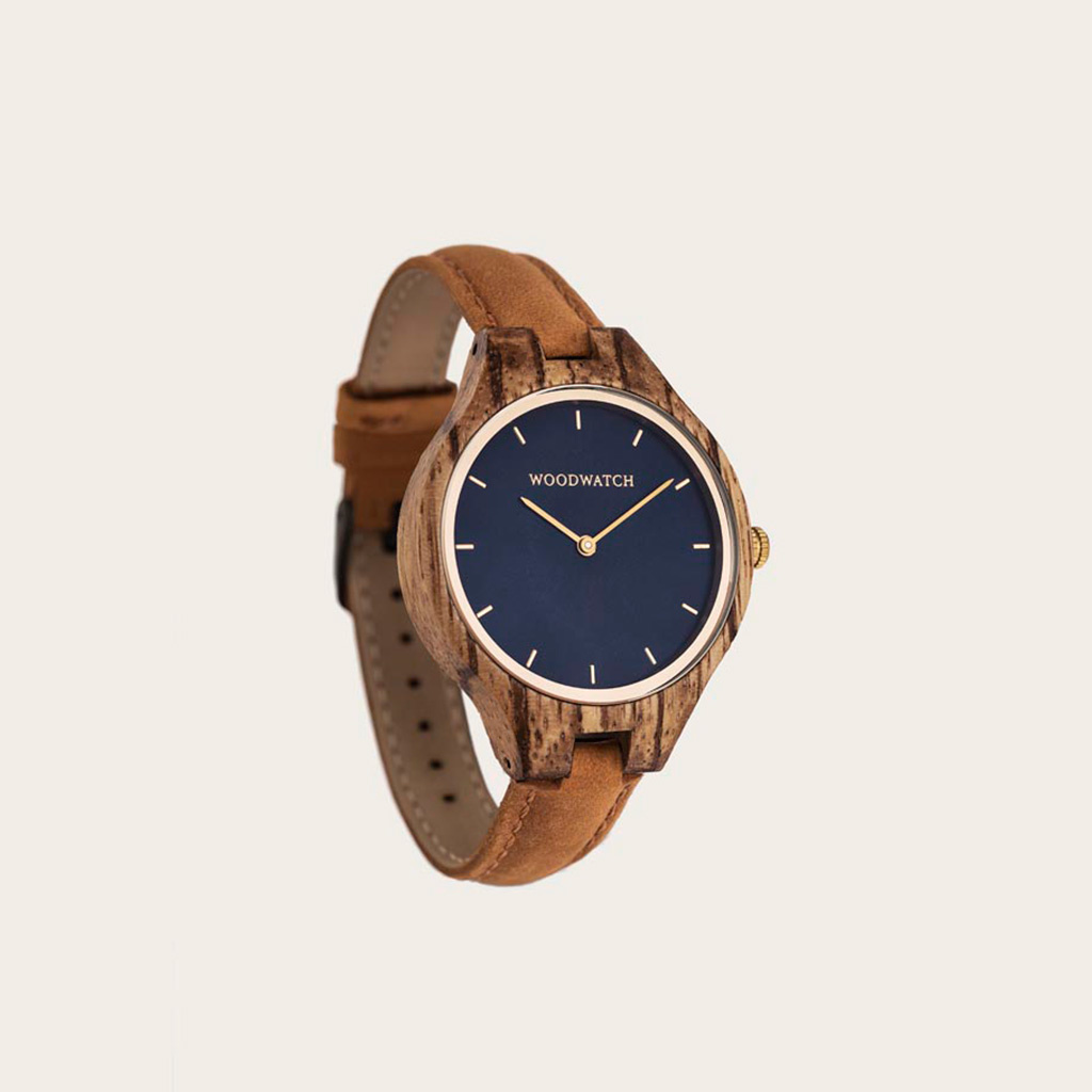 The AURORA Collection breaths the fresh air of Scandinavian nature and the astonishing views of the sky. This light weighing watch is made of West-African Zebrawood, accompanied by a blue stainless-steel dial with golden details.<br />