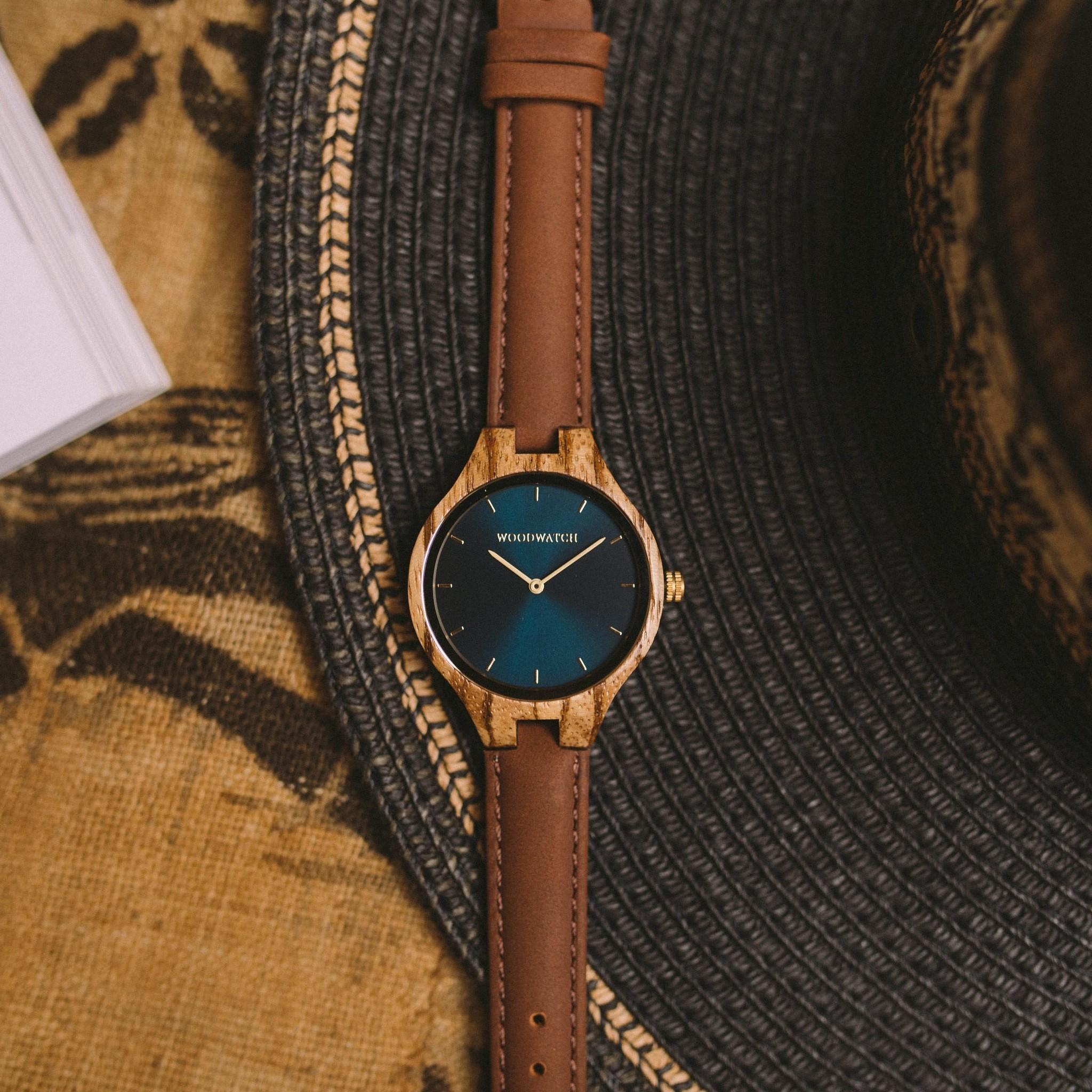 Die Uhren der AURORA Kollektion sind den unendlichen Weiten Skandinaviens nachempfunden und laden zum Träumen ein. Bei diesem leichten Modell wird westafrikanisches Zebranoholz von einem blauen Ziffernblatt aus Edelstahl und goldenen Elementen begleitet –