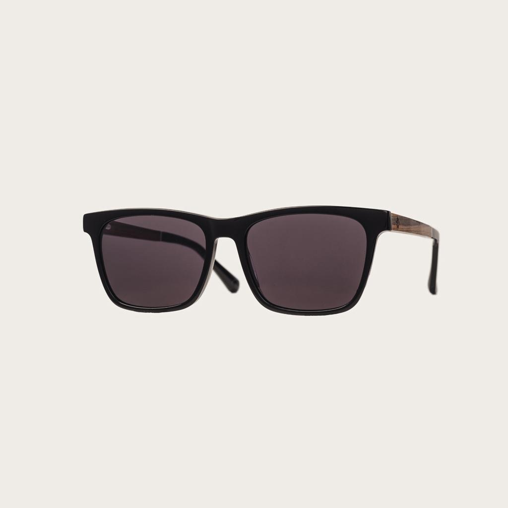 BROOKLYN All Black heeft een rechthoekig zwart montuur met zwarte glazen. Gemaakt van duurzaam Mazzuchelli bio-acetaat uit Italië en handmatig afgewerkt met natuurlijke rozenhouten poten met zwarte uiteinden van acetaat. Bio-acetaat is gemaakt van katoen