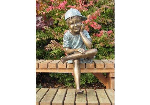 BronzArtes Bronzestatue: Sitzender Junge mit Mütze